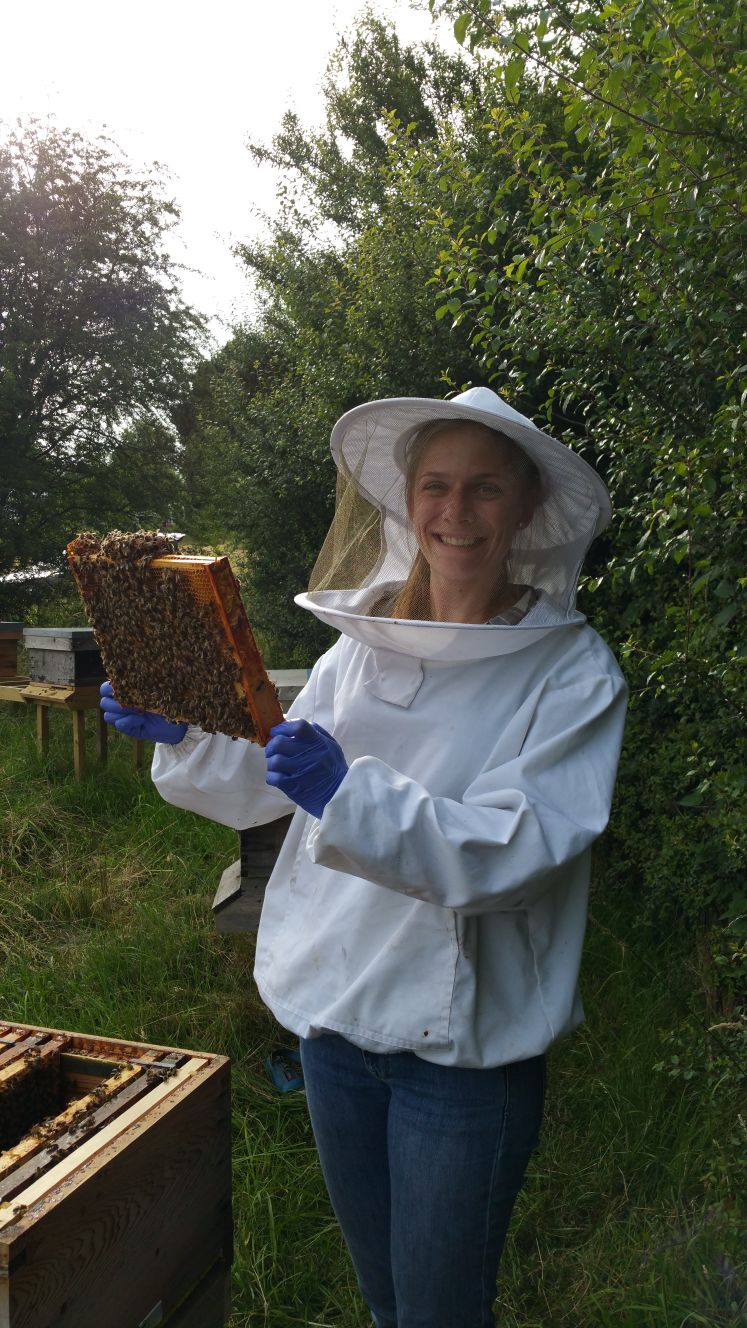 Female Beekeeper holding tray with bees